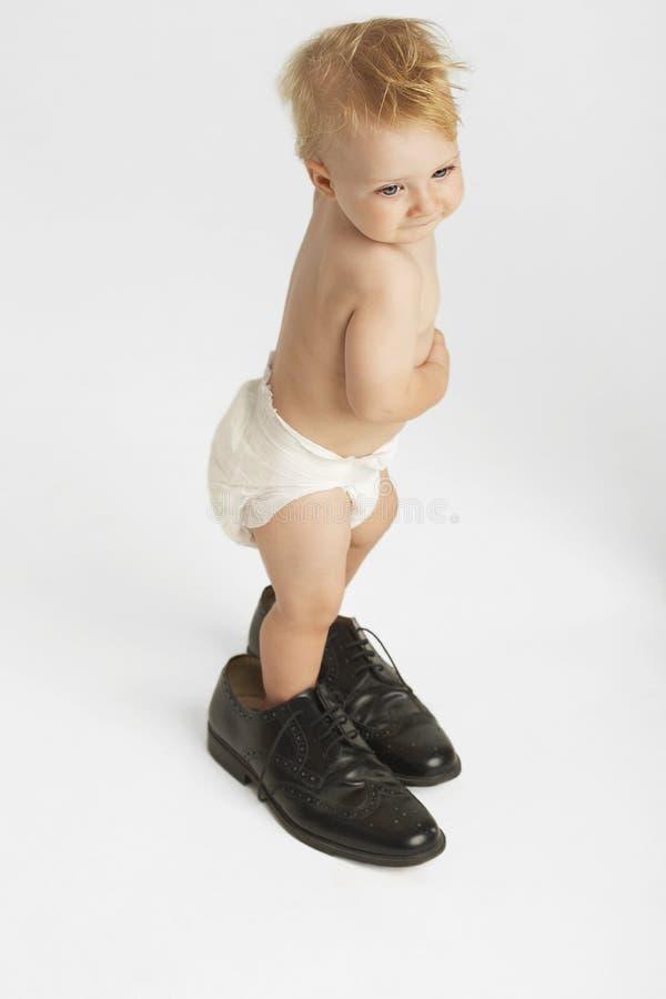 Le scarpe degli uomini d'uso del bambino sveglio immagini stock