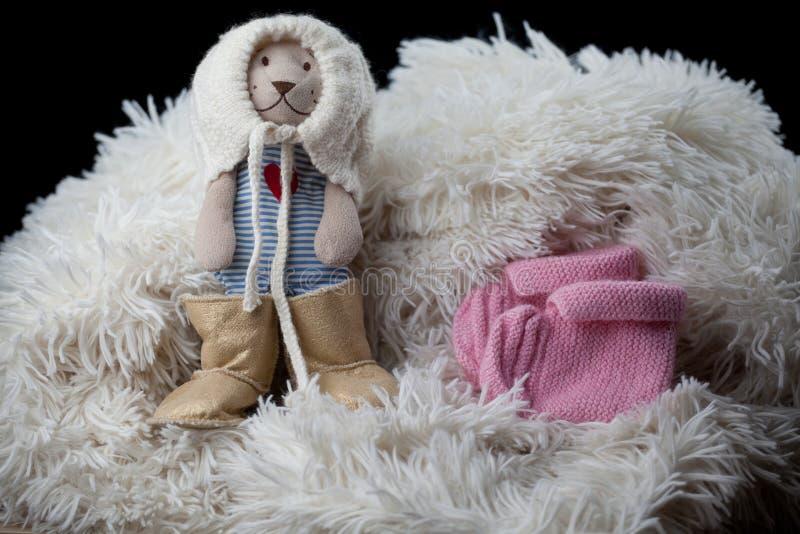 Le scarpe dei vestiti della lana del neonato giocano l'orso fotografia stock