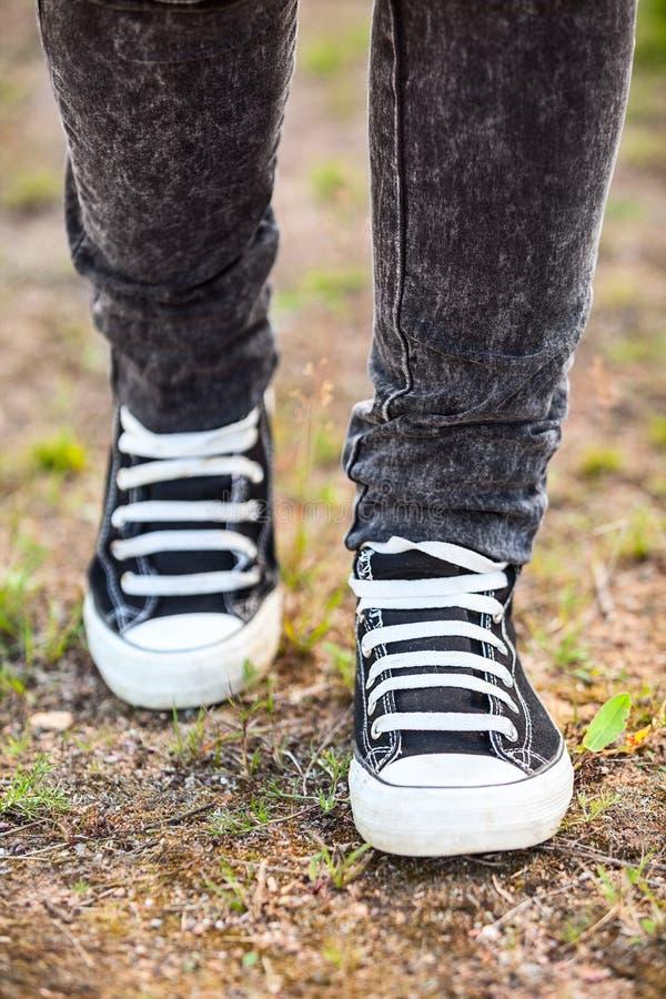 Le scarpe di gomma correnti sono sulle gambe, persona che cammina sulla terra, verticale fotografia stock
