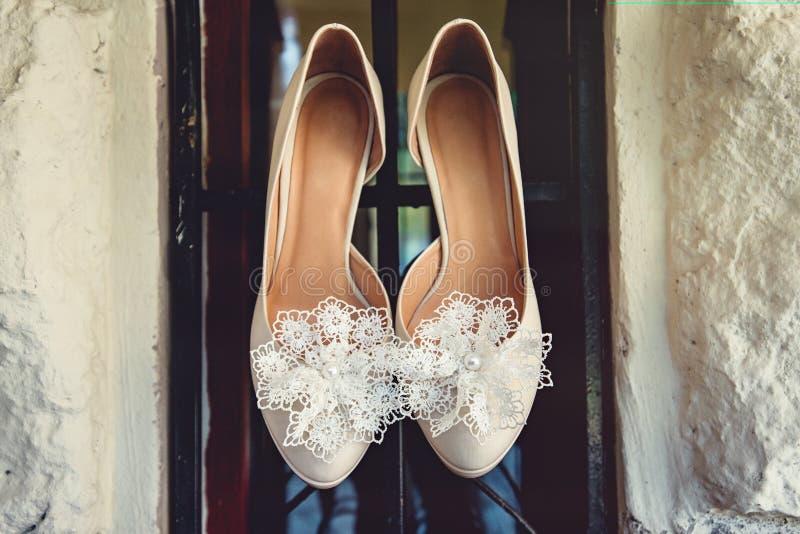 Le scarpe di lusso di nozze dell'avorio con pizzo fioriscono su, per la sposa, il fuoco selettivo fotografie stock