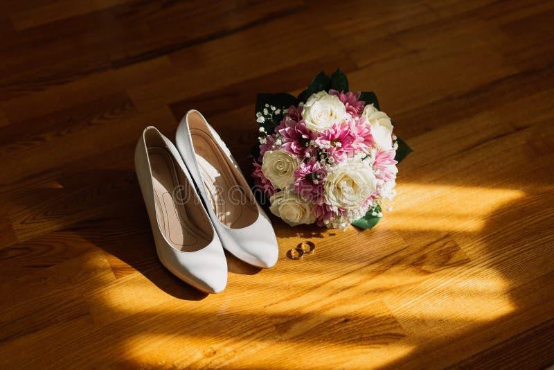 Le scarpe di nozze delle spose con un mazzo con le rose ed altri fiori sul tha armano la sedia immagini stock