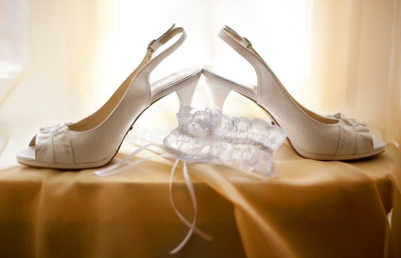 Le scarpe di nozze e il ` bianchi s della sposa merlettano la giarrettiera fotografie stock libere da diritti