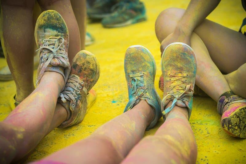 Le scarpe e le gambe variopinte degli adolescenti all'evento di funzionamento di colore immagini stock