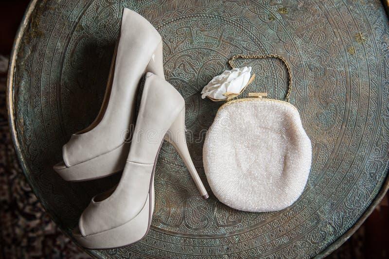 Le scarpe e la frizione delle donne di nozze sul vassoio d'ottone con un ornamento fotografia stock libera da diritti