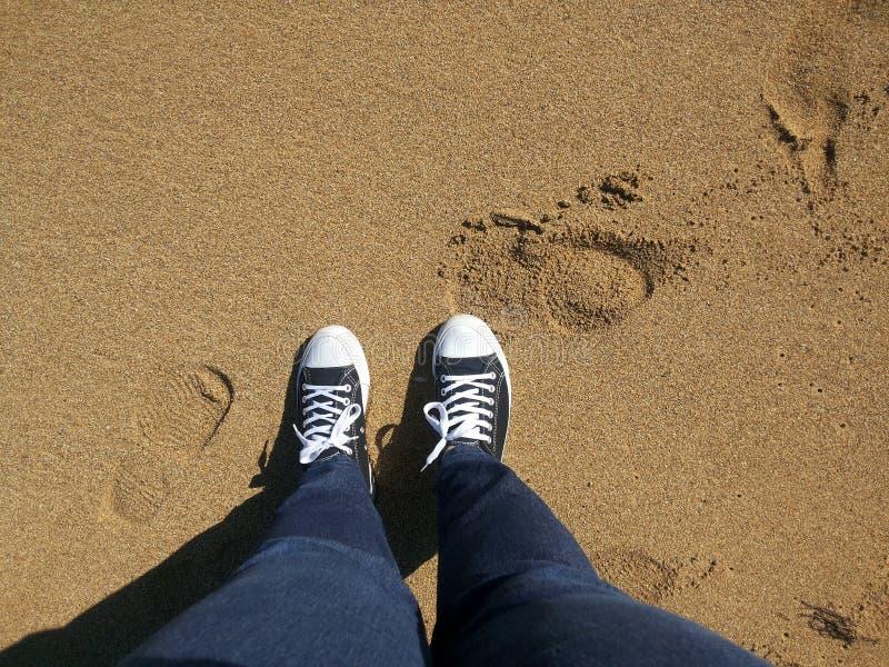 Le scarpe nella sabbia fotografie stock