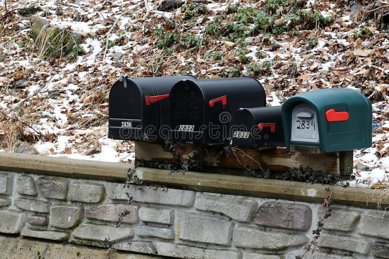 Le 4 scatole della posta sono parallelamente fuori in una zona rurale fotografia stock