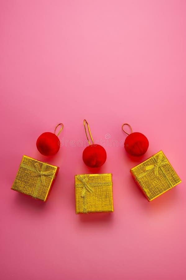 Le scatole di Natale dorate e le palle rosse si trovano su un fondo rosa immagine stock libera da diritti