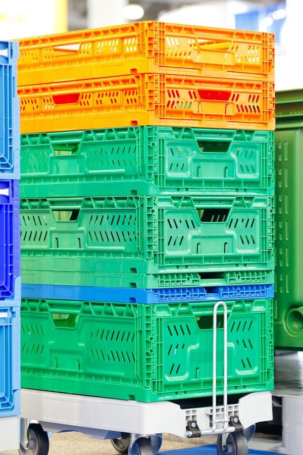 Le scatole di plastica variopinte hanno impilato uno sopra l'altro sul carrello del magazzino o sul carrello della piattaforma fotografia stock libera da diritti