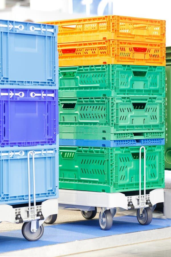 Le scatole di plastica variopinte hanno impilato uno sopra l'altro sul carrello del magazzino o sul carrello della piattaforma fotografie stock libere da diritti