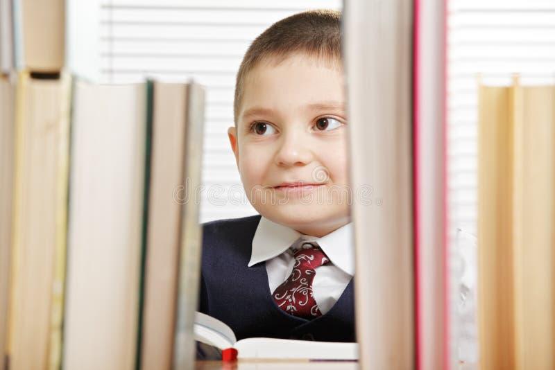Le schoolboy bak böcker arkivfoton