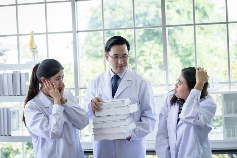 Le scientifique asiatique sup?rieur a assigner le nouveau travail aux ?tudiants dans le laboratoire photo stock