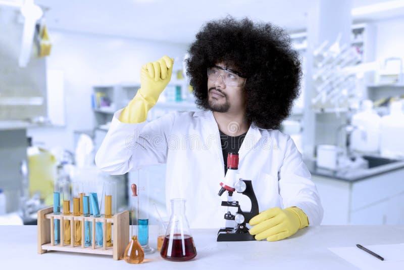 Le scientifique d'Afro tient la glissière de microscope photos libres de droits