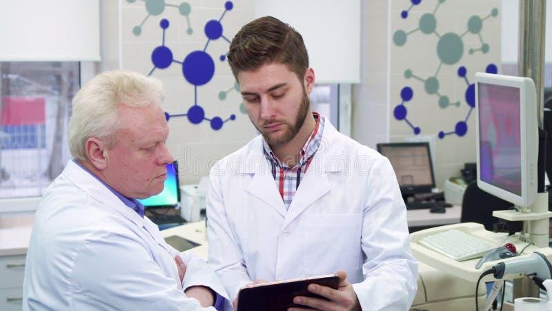 Le scientifique masculin montre quelque chose sur son comprimé à son collègue au laboratoire image libre de droits