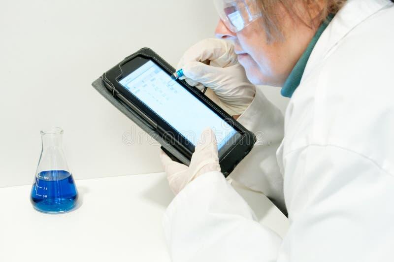Le scientifique saisit des données utilisant un stylo capacitif image stock