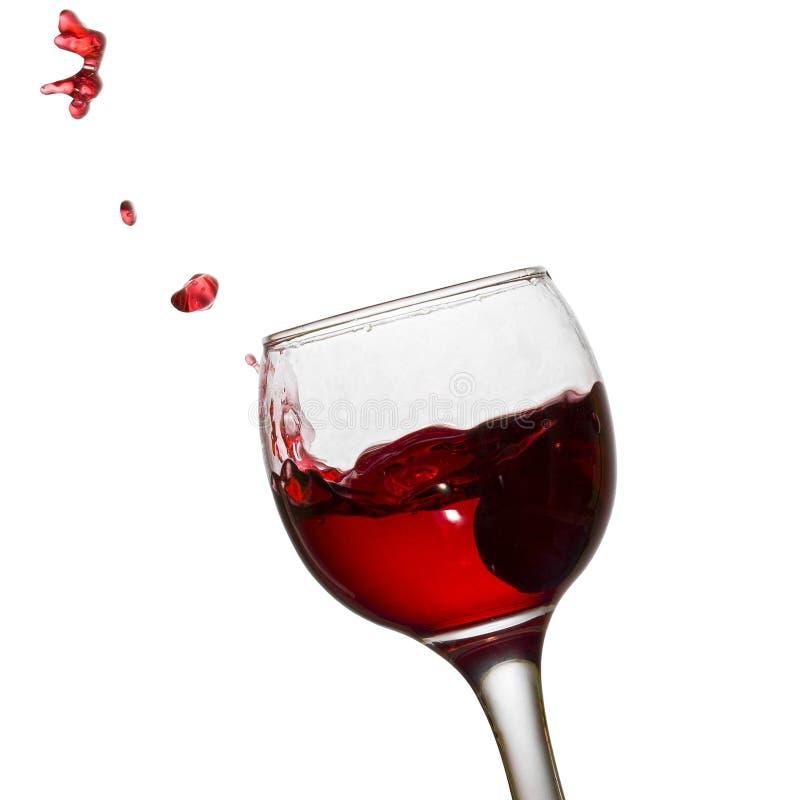 Le scintille luminose volano da un vetro di vino rosso fotografia stock