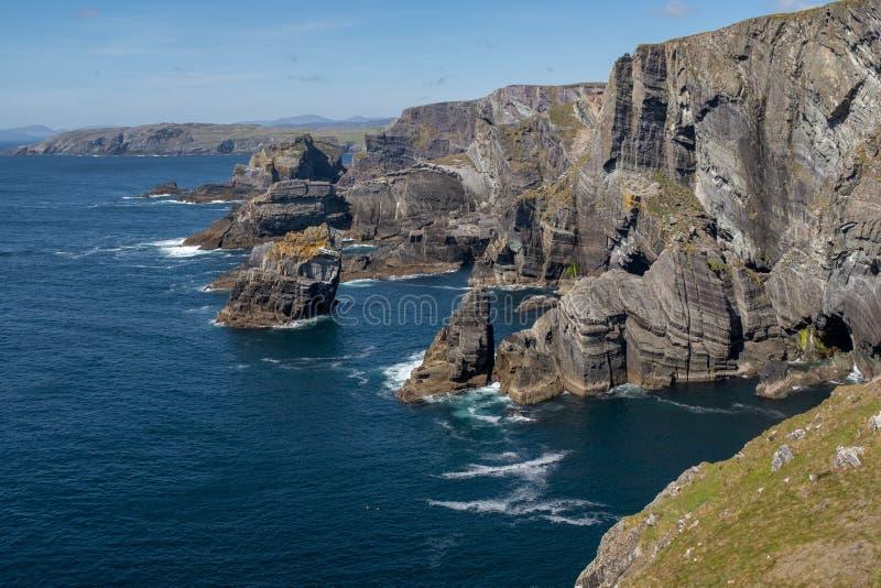 Le scogliere drammatiche alla testa di mezzana, sughero della contea, Irlanda dove gli arresti dell'Oceano Atlantico contro le ro immagini stock