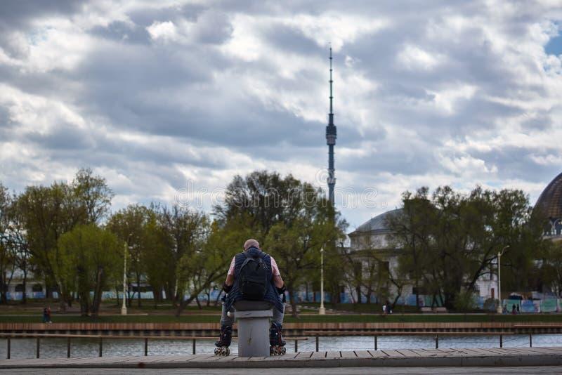 Le scooter plus âgé a un repos se reposant après avoir séparé des jambes au printemps image libre de droits