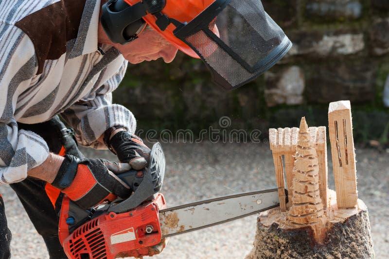 Le sculpteur découpe le bois avec la tronçonneuse photographie stock libre de droits