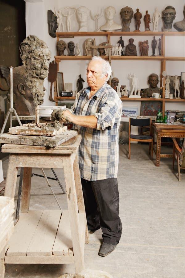 Le sculpteur plus âgé crée la tête photographie stock libre de droits