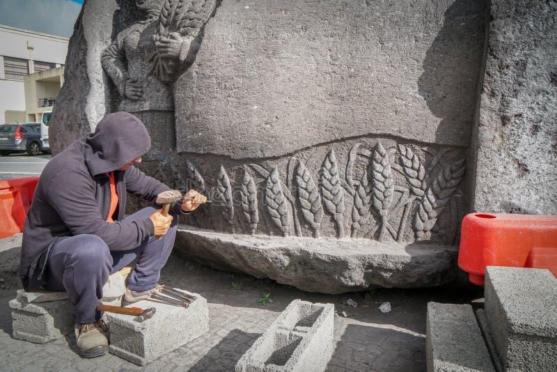 Le sculpteur travaille à une grande pierre images stock