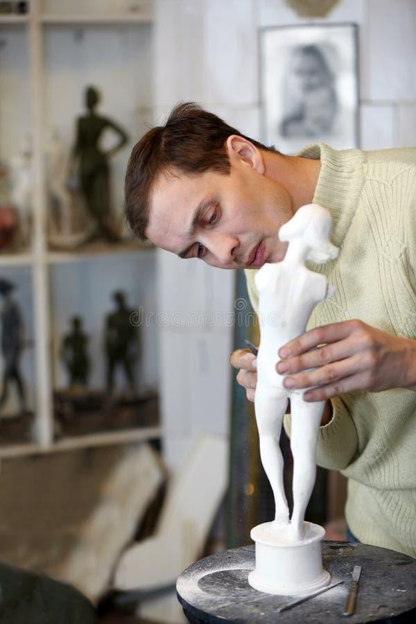 Le sculpteur travaille attentivement dans le studio photos stock
