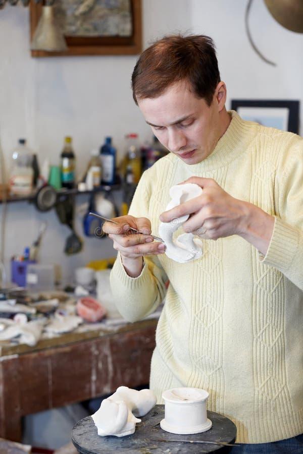 Le sculpteur travaille au fragment de la statuette. photos stock