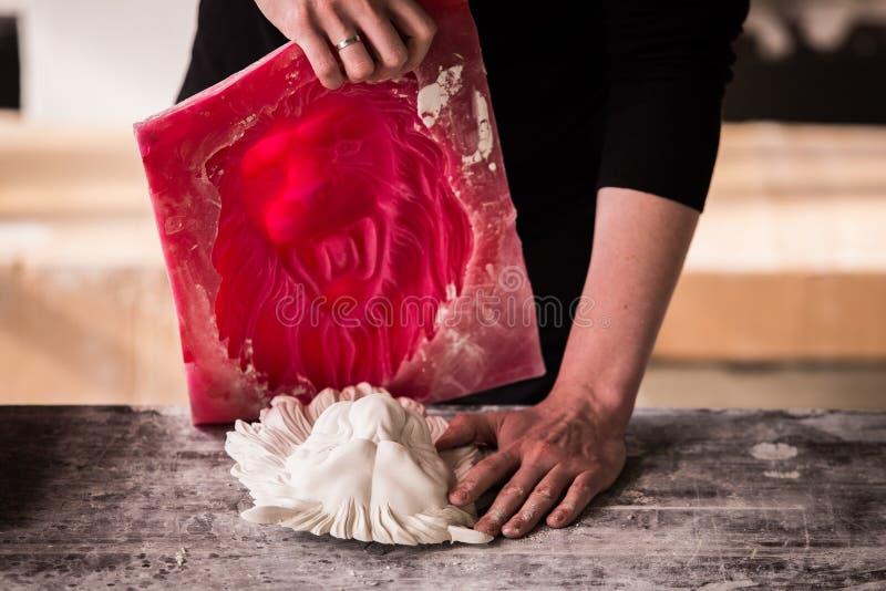 Le sculpteur travaille dans un atelier de plâtre Sépare le moule de silicone de la sculpture en plâtre de la tête du lion photos stock