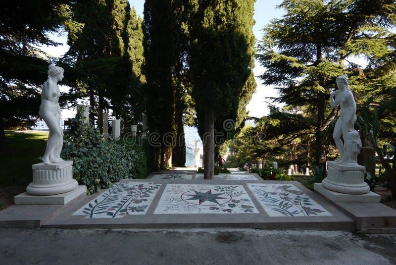 Le sculture bianche nel parco stanno stando dai lati differenti del percorso dai piatti con un modello separato vicino fotografie stock libere da diritti