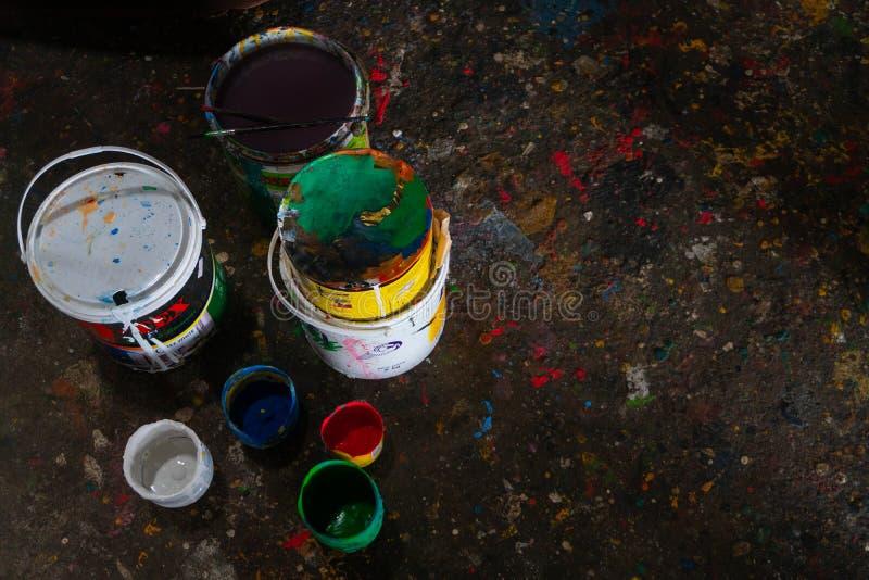 Le seau color? de peinture avec une brosse et le plancher est rempli de belle couleur solide parce que la peinture est dispers?e photos libres de droits