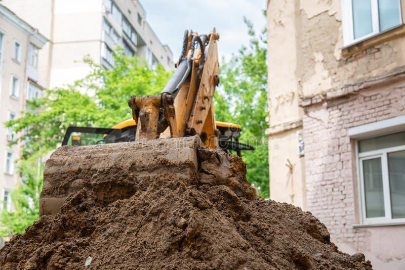 Le seau d'excavatrice verse la terre Tuyauterie de travail de r?paration photos libres de droits