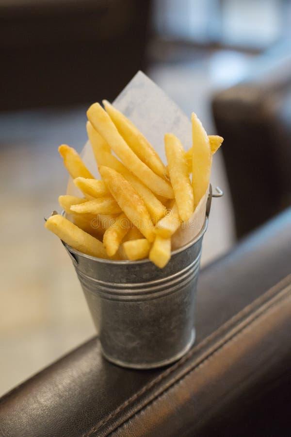Le seau en métal est rempli de coûts de pommes frites sur une chaise de retour image libre de droits