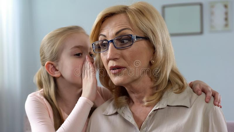 Le secret de chuchotement de petite fille aux cheveux longs a étonné le grandmom, connexion de famille photos libres de droits