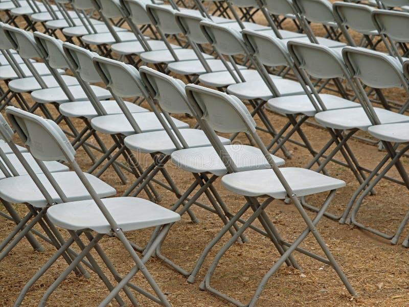 Le sedie bianche su terra sabbiosa hanno allineato per una presentazione, un evento, una manifestazione, una conferenza, una conf immagini stock