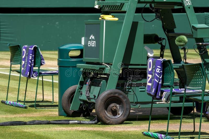 Le sedie del ` dei giocatori con l'asciugamano hanno ripiegato la parte posteriore e un ombrello verde e porpora sull'erba immagini stock