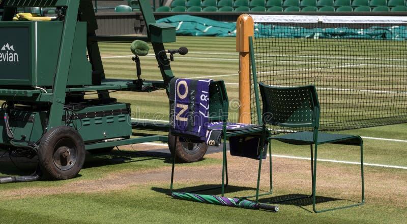 Le sedie del ` dei giocatori con l'asciugamano hanno ripiegato la parte posteriore e un ombrello verde e porpora sulla terra L'as immagine stock libera da diritti