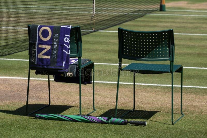 Le sedie del ` dei giocatori con l'asciugamano hanno ripiegato la parte posteriore e un ombrello verde e porpora sulla terra L'as fotografia stock libera da diritti