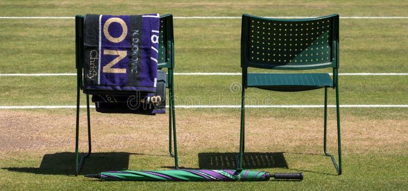 Le sedie del ` dei giocatori con l'asciugamano hanno ripiegato la parte posteriore e un ombrello verde e porpora sulla terra L'as immagine stock