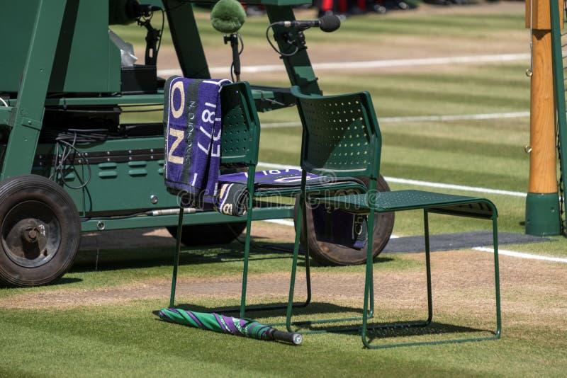 Le sedie del ` dei giocatori con l'asciugamano hanno ripiegato la parte posteriore e un ombrello verde e porpora sulla terra L'as fotografia stock