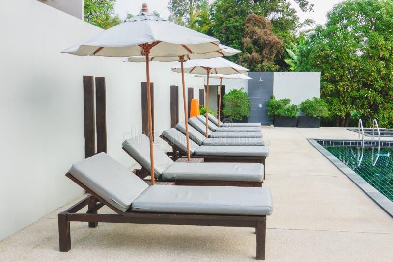 Le sedie di spiaggia si avvicinano alla piscina in hotel fotografie stock libere da diritti