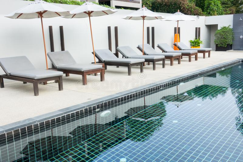 Le sedie di spiaggia si avvicinano alla piscina in hotel immagine stock libera da diritti
