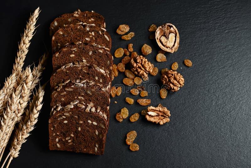 Le seigle foncé, pain de céréale avec des graines de tournesol, a dispersé des raisins secs, les écrous, flocons de blé sur un pa photo stock