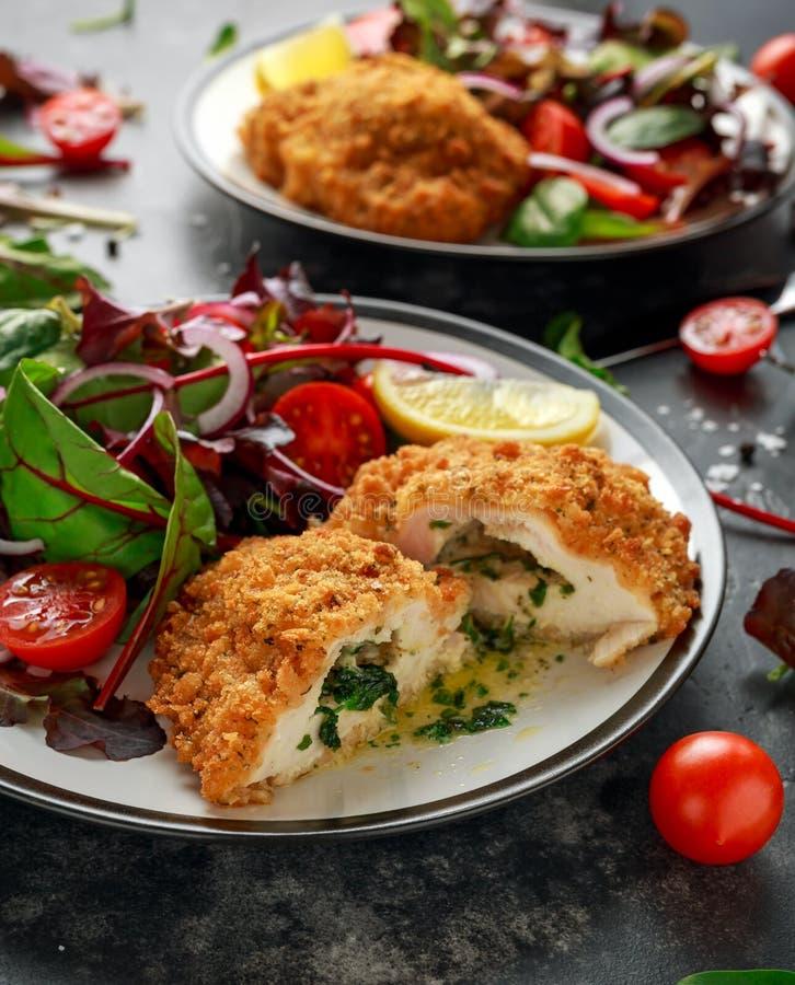 Le sein pané de Kiev de poulet bourré du beurre, de l'ail et des herbes a servi avec des légumes dans un plat photos libres de droits
