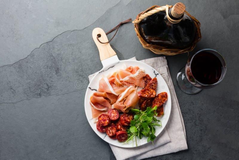 Le serrano espagnol et le salami de jambon sur le blanc marbrés plaquent un vin rouge Vue supérieure images libres de droits