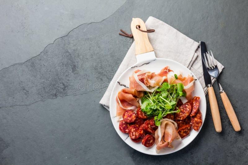 Le serrano et le salami espagnols de jambon sur le blanc ont marbré le plat Vue supérieure Copiez l'espace photos libres de droits