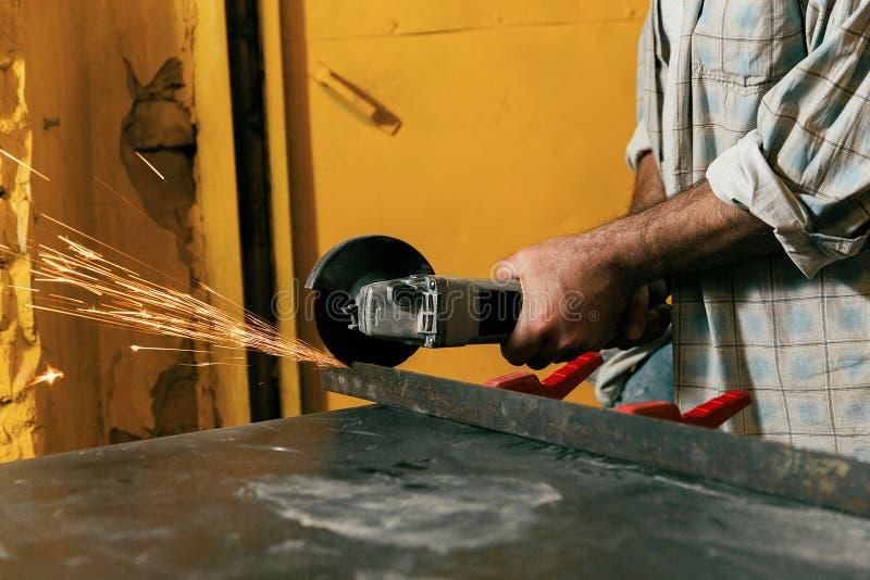 Le serrurier coupe le métal dans l'atelier photos libres de droits