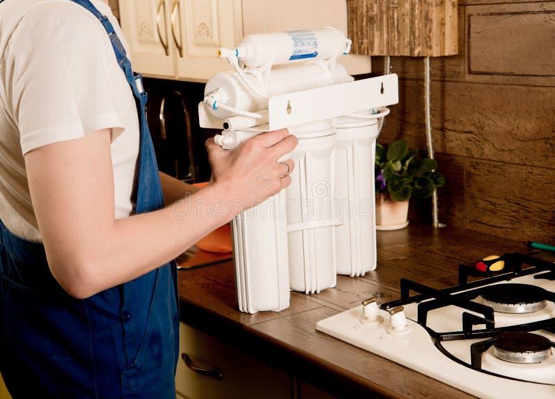 Le serrurier installe le filtre d'eau image stock