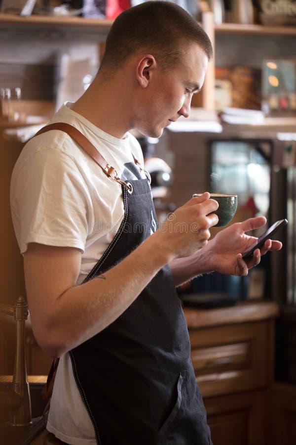 Le serveur agréable regarde l'écran du téléphone portable Surfez le réseau photos stock