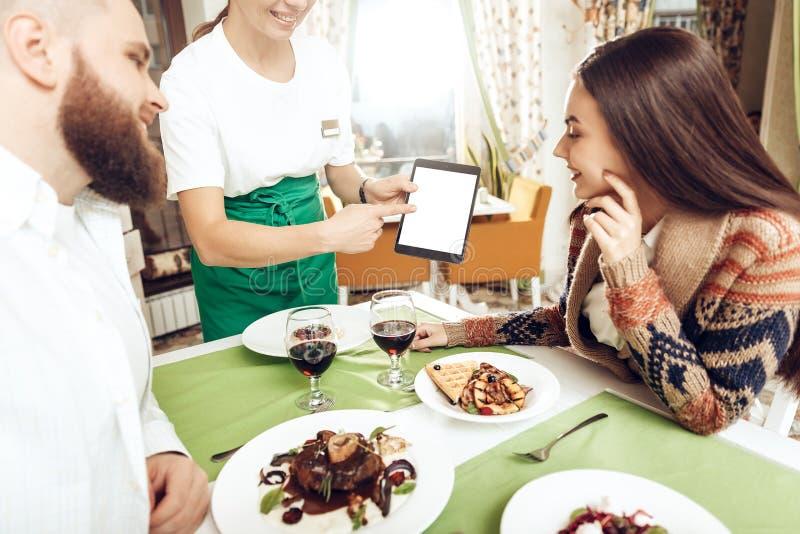 Le serveur de fille prend un ordre d'un jeune couple images stock