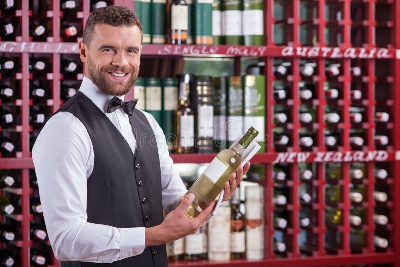 Le serveur masculin gai travaille dans la vin-cave photo stock