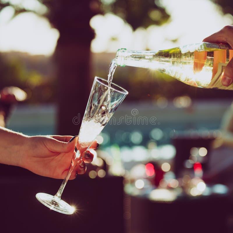Le serveur pourring le vin mousseux dans un verre de femme à l'outd photo libre de droits